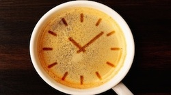 Cup of coffee with clock face imprint in coffee