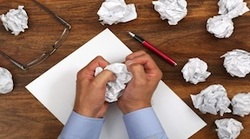 Man scrunching up paper at desk